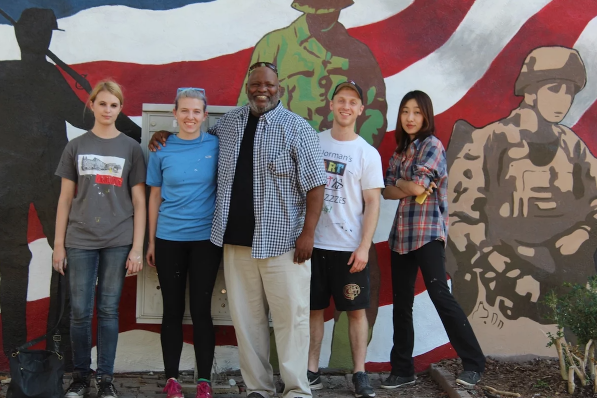 Professor Joseph Norman (center) with students in front of a mural they created to honor veterans.