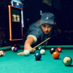 Person shooting pool wearing a baseball cap