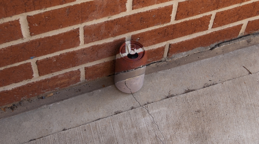 A can is painted to camouflage into a brick wall and sidewalk