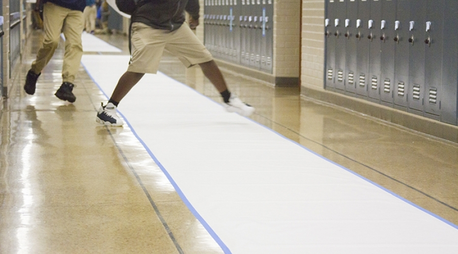 Feet of students walking along a piece of paper in the school hallway