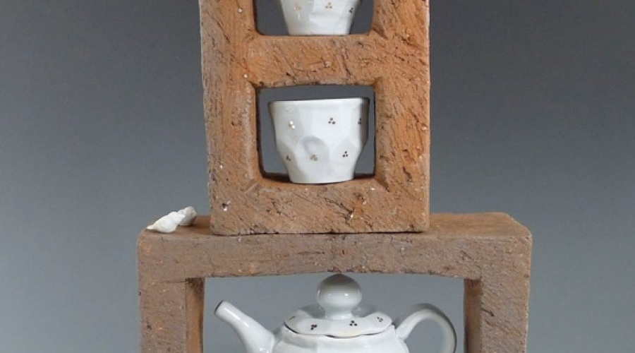 A tea pot and two tea cups sit on top of cinder blocks
