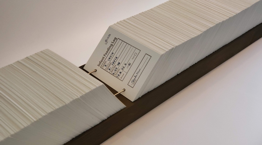Sarah Irvin, (detail) Infant Feeding Log, 2018, Card catalogue with 2,400 unique platen-pressed cards, metal rods, wooden base, 7 x 78 1/4 inches