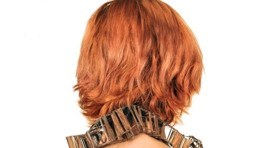 A rectangular necklace rests on the neck of a model with red hair