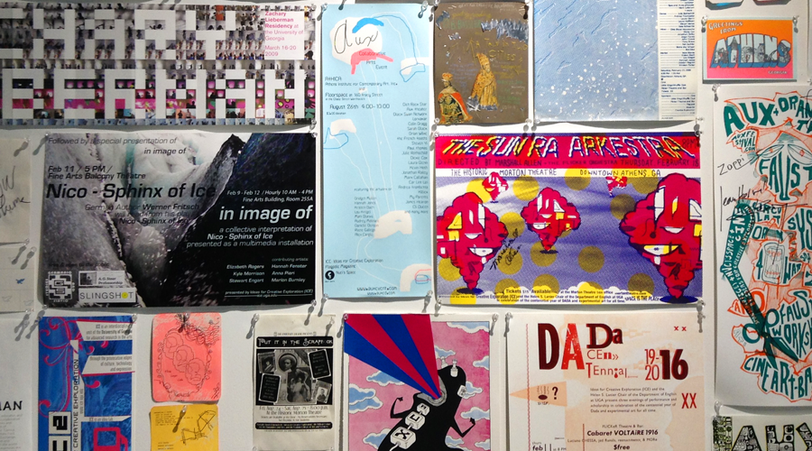 An array of student made posters hang on a wall