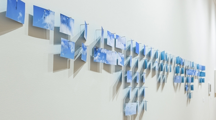 A bunch of different images of a blue sky hang on a wall