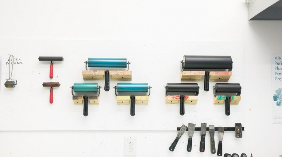 Print rollers hang on a wall in a classroom