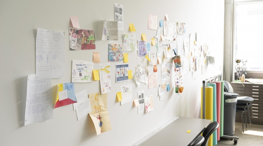 Different pieces of children's artwork hangs on a wall